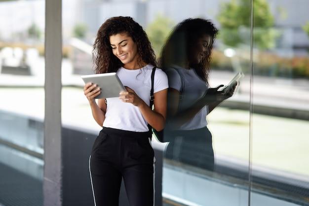 Mujer árabe joven feliz que usa la tableta digital en negocio.