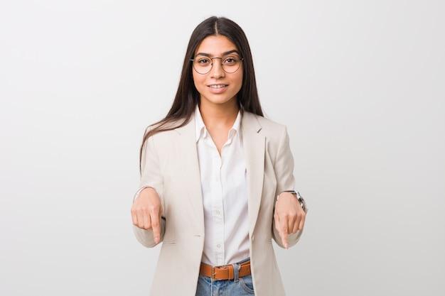 La mujer árabe joven del negocio aislada contra un blanco señala abajo con los dedos, sensación positiva.