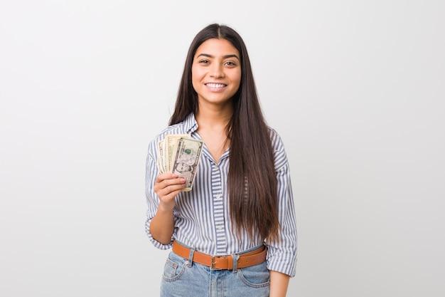 Mujer árabe joven que lleva a cabo dólares felices, sonrientes y alegres.