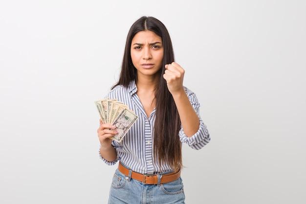 Mujer árabe joven que lleva a cabo dólares que muestran el puño con la expresión facial agresiva.