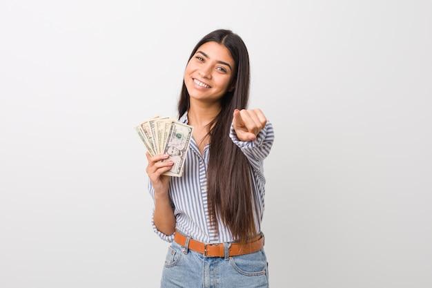 Mujer árabe joven que lleva a cabo sonrisas alegres de los dólares que señalan al frente.