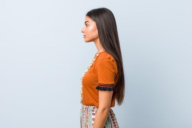 La mujer árabe joven que mira a la izquierda, de lado plantea.