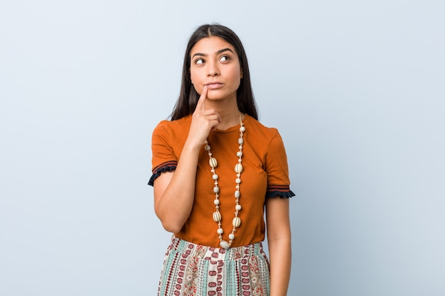 Mujer árabe joven que mira de lado con expresión dudosa y escéptica.