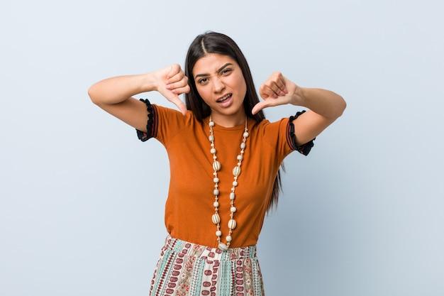Mujer árabe joven que muestra el pulgar hacia abajo y que expresa aversión.