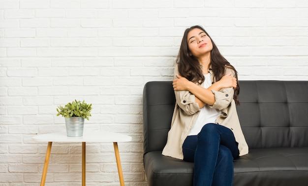 La mujer árabe joven que se sienta en el sofá abraza, sonriendo despreocupada y feliz.