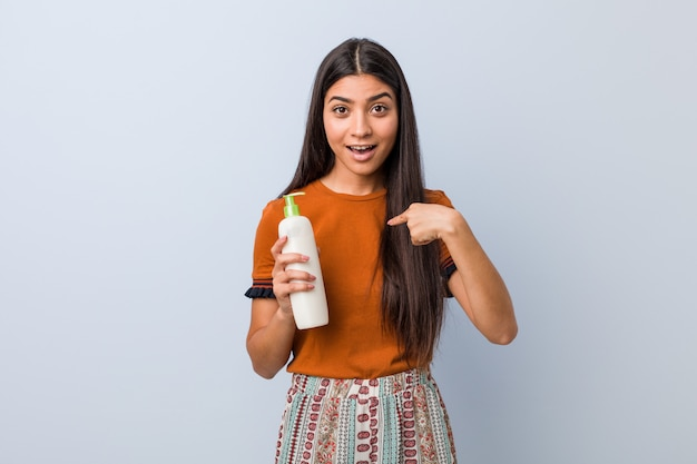 La mujer árabe joven que sostenía una botella poner crema sorprendió señalar a sí mismo, sonriendo ampliamente.
