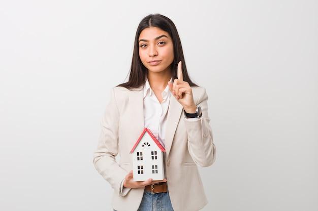 Mujer árabe joven que sostiene un icono de la casa que muestra el número uno con el dedo.