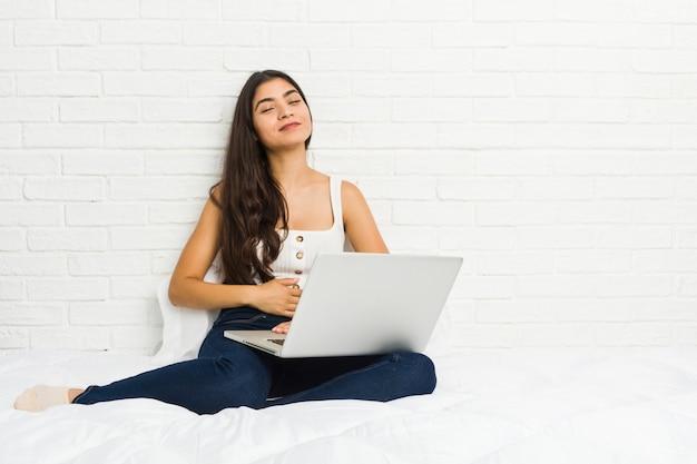 La mujer árabe joven que trabaja con su computadora portátil en la cama toca la panza, sonríe suavemente, comiendo y concepto de la satisfacción.