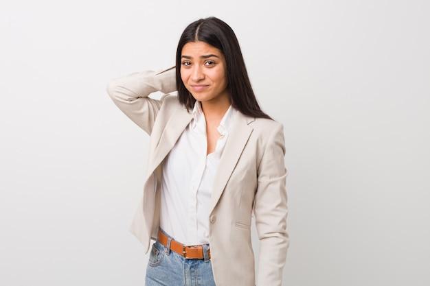 Mujer árabe del negocio joven aislada contra un fondo blanco que toca detrás de la cabeza, pensando y tomando una decisión.