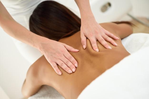 Mujer árabe que recibe un masaje en la espalda en un centro de spa.