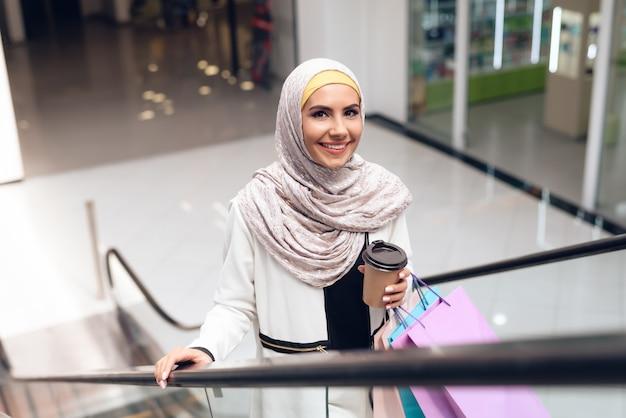 Mujer árabe con taza de café de pie en el centro comercial.