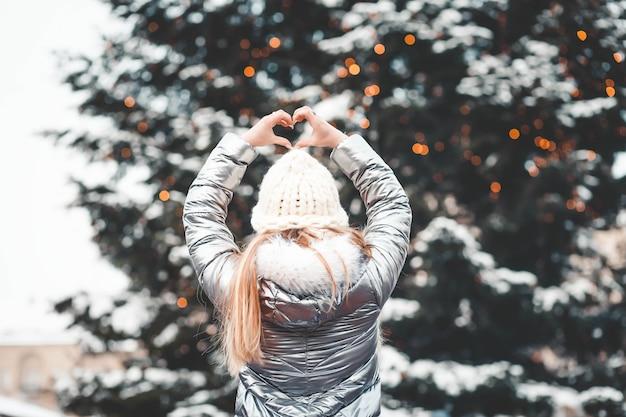 Mujer con el árbol de navidad muestra el corazón