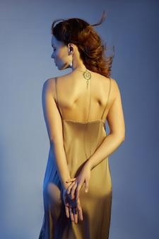 Mujer con aretes y cadena dorada