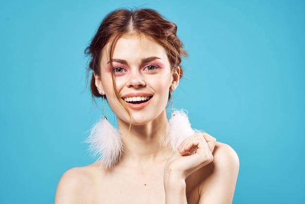 Mujer con aretes esponjosos maquillaje brillante posando de cerca