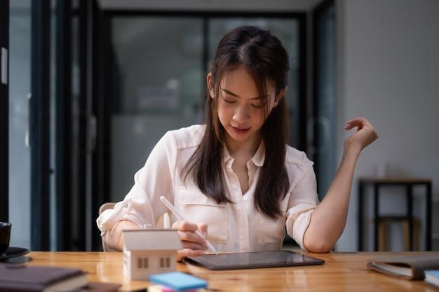 Mujer arquitecta que usa una aplicación de tableta digital para dibujar a mano una casa de diseño con un modelo en un escritorio de madera. idea de propiedad en el sector inmobiliario.