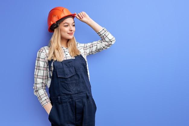 Mujer arquitecto en overoles aislado sobre fondo azul de estudio, mujer joven en casco naranja posando a la cámara y mirando al lado
