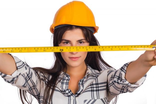 Mujer de arquitecto sosteniendo una cinta métrica.