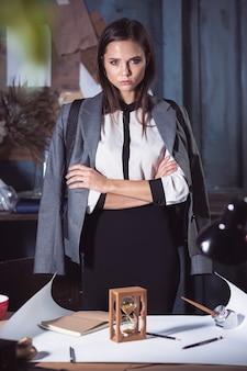 Mujer arquitecto trabajando en la mesa de dibujo en la oficina o en casa con reloj de arena. concepto de falta de tiempo