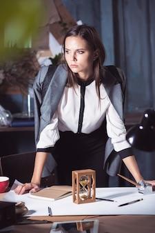 Mujer arquitecto trabajando en la mesa de dibujo en la oficina o en el hogar.