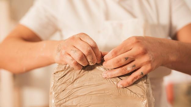 Mujer arrancando la tapa de la arcilla.