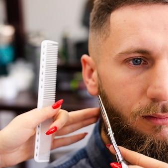 Mujer arreglando la barba de un cliente