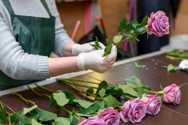 Mujer arreglando elegantes flores de color púrpura