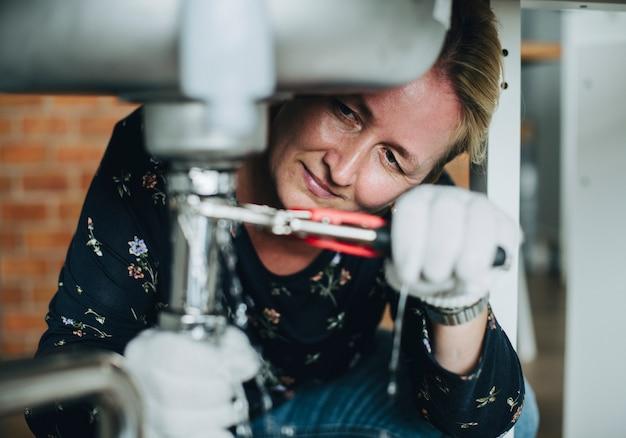 Mujer arreglando un fregadero de cocina