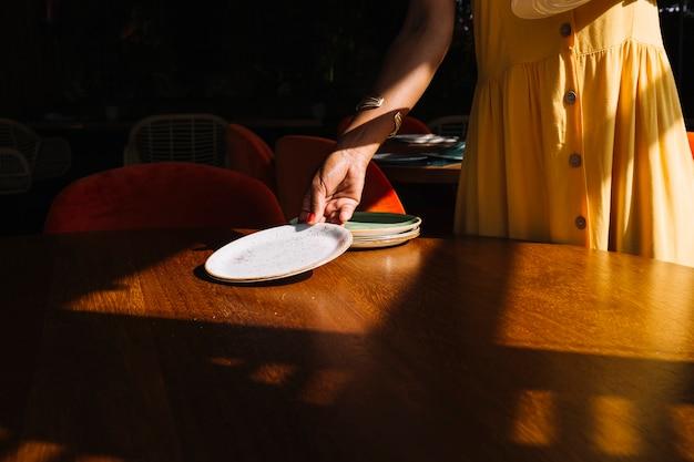 Mujer arreglando los platos en mesa de madera