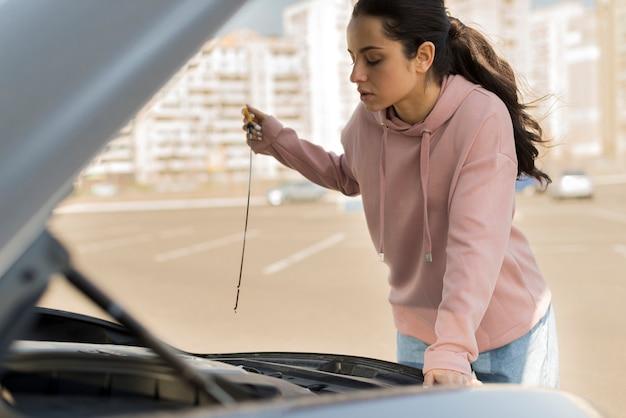 Mujer arreglando su auto cerca de la ciudad