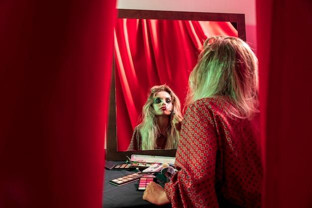 Mujer arreglando su maquillaje en el espejo