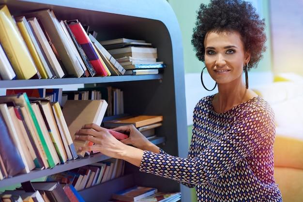 Mujer arrodillada junto a la estantería