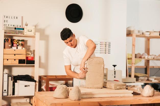 Mujer artesana abriendo la tapa del taller.