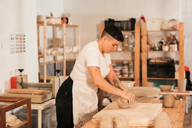 Mujer artesana amasando la arcilla en mesa de madera