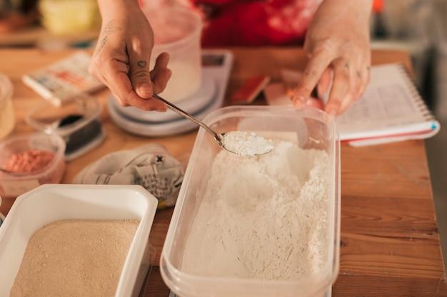 Mujer artesana tomando polvo de color cerámico con cuchara del recipiente.