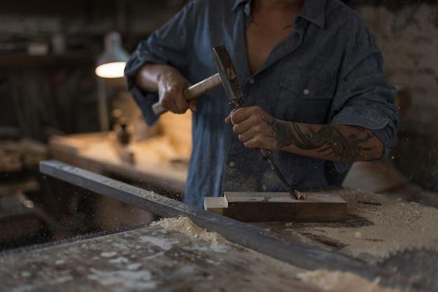 Mujer artesana está trabajando en el taller. concepto hecho a mano y hobby. manos femeninas con un primer plano de martillo