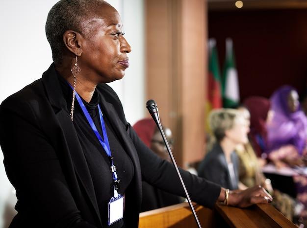 Una mujer de ascendencia africana hablando en un micrófono