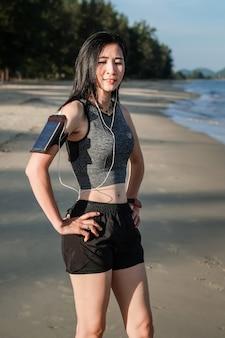 Mujer de asia en las mercancías del deporte que ejercita y que corre en la playa.