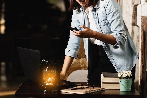 Mujer de asia que usa el teléfono inteligente que trabaja en el tiempo libre con feliz.