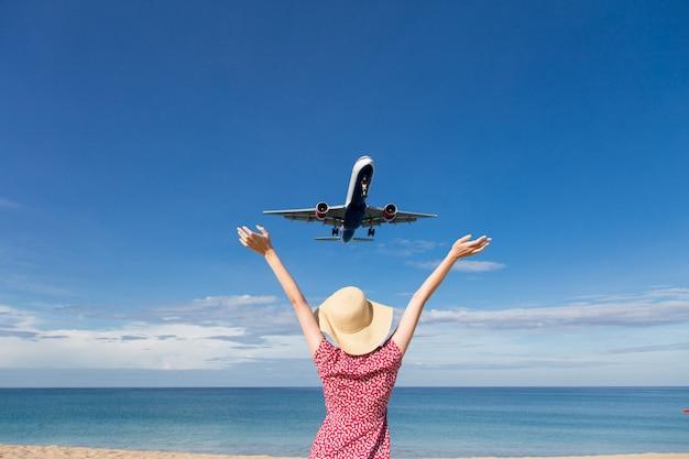 Mujer de asia que viaja, relaja vacaciones y mira el avión volando sobre el mar