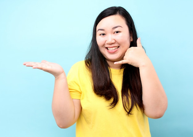 La mujer de asia del retrato finge contestar al teléfono para invitar, aislado en fondo azul en estudio.