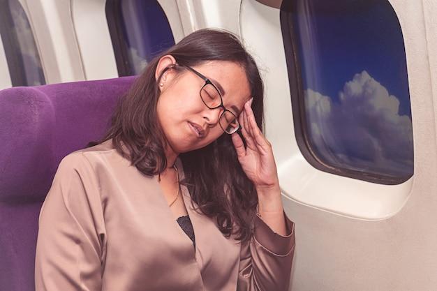 Mujer de asia sufre de dolor de cabeza dentro del avión
