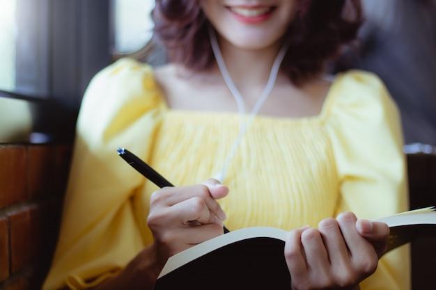 Mujer de asia trabajando y escuchando música con feliz.