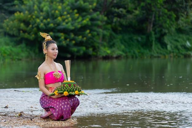 Mujer de asia en traje tailandés tradicional mantenga kratong. festival de loy krathong