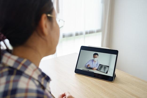 Mujer asiática de 30 a 35 años con tableta, ver los resultados del examen de los médicos en un control remoto