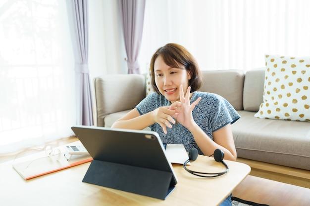 Mujer asiática de 30 a 35 años con tableta, viendo la lección curso en línea de lenguaje de señas