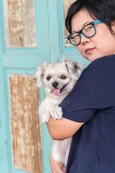 Mujer asiática abrazando perro tan lindo con pared de madera