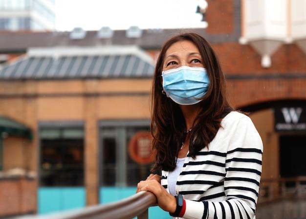 Mujer asiática con un abrigo azul caminando por la ciudad de europa