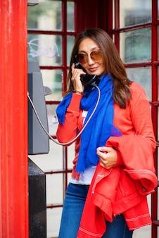 Mujer asiática con abrigo rojo, jeans, bufanda azul y camisa blanca tener una conversación telefónica en la cabina telefónica roja
