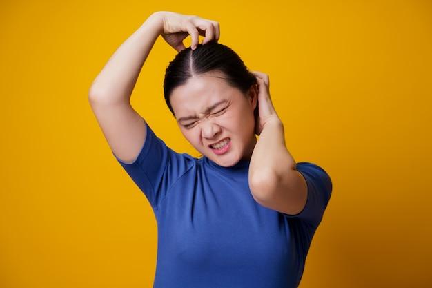 Mujer asiática aburrida y molesta, rascándose la cabeza, en amarillo.