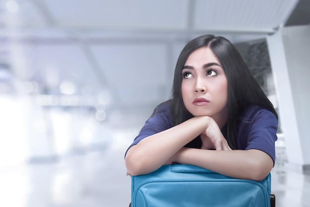 Mujer asiática aburrida del viajero con la maleta que espera su vuelo